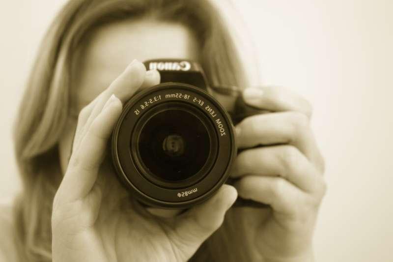 美女拿着相机正在拍摄图片素材